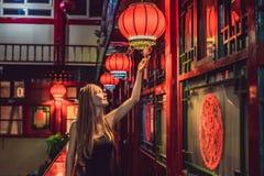 De jonge vrouwentoerist bekijkt de Chinese traditionele lantaarns Chinees Nieuwjaar Reis naar het concept van China stock foto