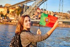 De jonge vrouwentoerist die met Portugese vlag van mooie landschapsmening over de oude stad met rivier en beroemd ijzer genieten  stock afbeeldingen