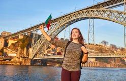 De jonge vrouwentoerist die met Portugese vlag van mooie landschapsmening over de oude stad met rivier en beroemd ijzer genieten  royalty-vrije stock afbeeldingen