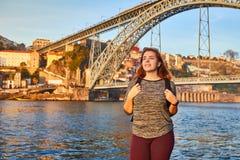 De jonge vrouwentoerist die van mooie landschapsmening over de oude stad met rivier en beroemd ijzer genieten overbrugt Dom Luiz  royalty-vrije stock afbeelding