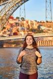 De jonge vrouwentoerist die van mooie landschapsmening over de oude stad met rivier en beroemd ijzer genieten overbrugt Dom Luiz  stock afbeelding