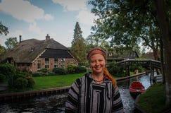 De jonge vrouwentoerist in etnische sweater en bandana bevindt zich tegen de achtergrond van het beroemde dorp van Githorn stock afbeeldingen