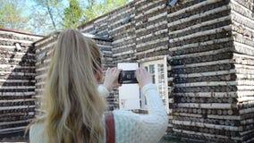 De jonge vrouwentoerist met een lang eerlijk haar doet video op de mobiele telefoon van de Berk onderbrengt en het Maskerportaal stock videobeelden