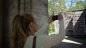 De jonge vrouwentoerist met een lang eerlijk haar doet video op de mobiele telefoon van de Berk onderbrengt en het Maskerportaal stock video