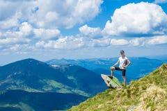 De jonge vrouwentoerist op klippen` s rand van bergen geniet van de mening Royalty-vrije Stock Foto