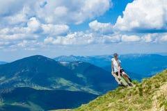 De jonge vrouwentoerist op klippen` s rand van bergen geniet van de mening Stock Afbeeldingen