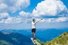 De jonge vrouwentoerist op klippen` s rand van bergen heft op hand op met geniet van en geluk Mooie mening van hemel op hoogste b Royalty-vrije Stock Foto