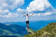 De jonge vrouwentoerist op klippen` s rand van bergen heft op hand op met geniet van en geluk Mooie mening van hemel op hoogste b Stock Fotografie