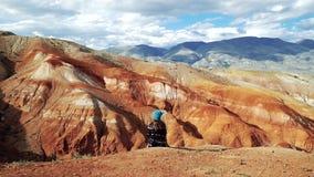 De jonge vrouwentoerist zit op de rand van een rode berg Er zijn toneellandschap en bewolkte hemel op de achtergrond stock video