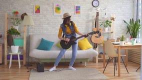 De jonge vrouwentuimelschakelaar speelt elektrische gitaar stock videobeelden