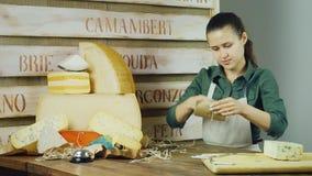 De jonge vrouwenverkoper pakt een stuk van kaas bij de teller in stock footage
