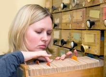De jonge vrouwenwerken met bibliotheekkaartsysteem royalty-vrije stock afbeeldingen