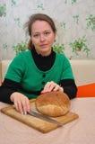 De jonge vrouwenzitting bij een lijst en treft voorbereidingen om eigengemaakt brood te snijden Stock Afbeeldingen