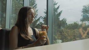De jonge vrouwenzitting dichtbij venster en drinkt cocktail stock video