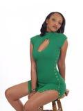 De jonge vrouwenzitting in groen breit kleding royalty-vrije stock afbeelding