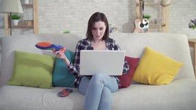 De jonge vrouwenzitting op de laag gebruikt laptop en houdt orthopedische binnenzolen in haar hand stock videobeelden