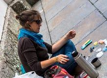 De jonge vrouwenzitting op de stoep maakt leuke decoratie van parels Stock Foto