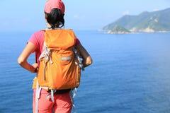 De jonge wandelaar van de geschiktheidsvrouw geniet van de mening over kustberg Royalty-vrije Stock Afbeelding