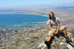 De jonge wandelaar zit op rots Royalty-vrije Stock Foto