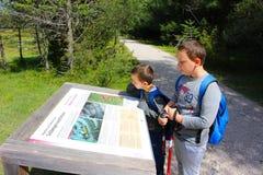De jonge wandelaars nemen een teken van het park op de weg langs het meer, Lago Di Dobbiaco, Dolomiet, Italië waar stock foto's