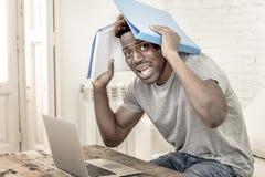 De jonge wanhopige en overweldigde zwarte mens van de afro Amerikaanse student in spanning thuis werken beklemtoond met laptop co stock foto's