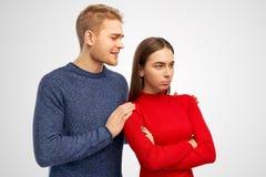 De jonge wanhopige Europese mens houdt schouders van meisje, kijkt met miserabele uitdrukking, vraagt om vergiffenis, voelt schul royalty-vrije stock afbeelding