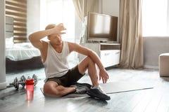 De jonge well-built mens gaat binnen voor sporten in flat Vermoeide uitgeputte kerel na training Hij zit op carimate op vloer en royalty-vrije stock foto