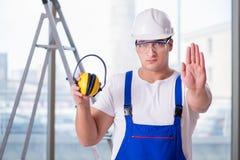 De jonge werknemer die met lawaai hoofdtelefoons annuleren stock fotografie