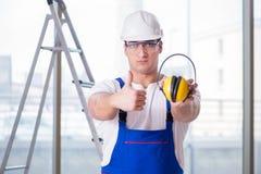 De jonge werknemer die met lawaai hoofdtelefoons annuleren royalty-vrije stock afbeelding