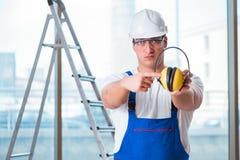 De jonge werknemer die met lawaai hoofdtelefoons annuleren stock foto's