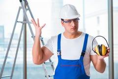 De jonge werknemer die met lawaai hoofdtelefoons annuleren stock afbeeldingen