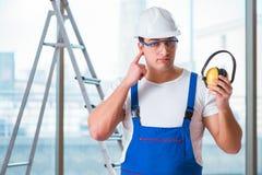 De jonge werknemer die met lawaai hoofdtelefoons annuleren stock foto