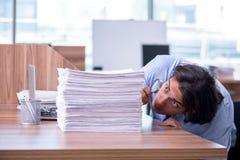De jonge werknemer ongelukkig met het bovenmatige werk royalty-vrije stock fotografie