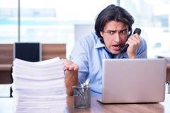 De jonge werknemer ongelukkig met het bovenmatige werk stock afbeeldingen