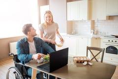 De jonge werknemer zit op rolstoel en bekijkt vrouw Hij werkt met laptop en eet salade Zij bekijken elkaar en glimlach stock foto