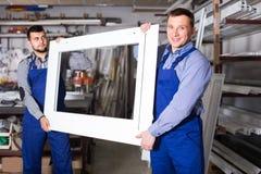 De jonge werknemers houdt samen het raamkozijn stock foto's