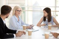 De jonge werknemers luisteren aan vrouwelijke werkgever die tijdens briefing spreken stock afbeeldingen