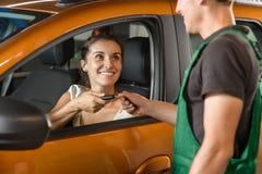 De jonge werktuigkundige overhandigt de sleutels van de auto aan het meisje royalty-vrije stock afbeelding