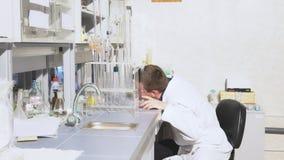 De jonge wetenschapper leidt chemische experimenten met vloeistoffen in het laboratorium stock videobeelden