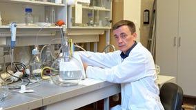 De jonge wetenschapper leidt chemische experimenten met vloeistoffen in het laboratorium stock footage