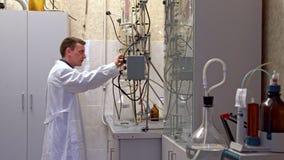 De jonge wetenschapper leidt chemische experimenten met vloeistoffen in het laboratorium stock video
