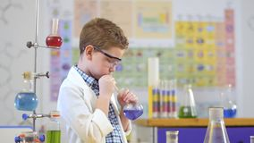De jonge wetenschapper maakt experiment met vloeistof in laboratorium stock video