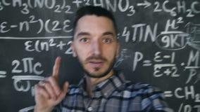 De jonge wetenschappermens die selfie schiet in chemisch en wiskundig de ruimtebinnenland van de vergelijkingenmuur maken stock videobeelden