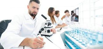 De jonge wetenschapperwerken in het laboratorium stock foto