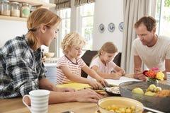 De jonge witte familie samen bezig in hun keuken, sluit omhoog royalty-vrije stock foto