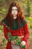 De jonge witte Kaukasische vrouw met grote blauwe ogen met lang rood haar zit in een rode middeleeuwse kleding met chaperon en ho royalty-vrije stock foto
