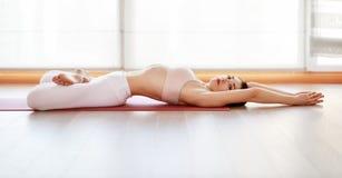 De jonge yoga van vrouwenpraktijken bij gymnastiek door venster stock foto