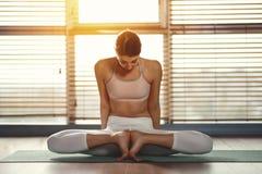 De jonge yoga van vrouwenpraktijken bij gymnastiek door venster royalty-vrije stock foto