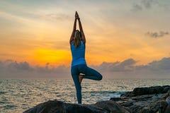 De jonge yoga van vrouwenpraktijken op de rotsen dichtbij het overzees bij dageraad op een tropisch eiland Stock Afbeelding