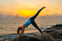 De jonge yoga van vrouwenpraktijken op de rotsen dichtbij het overzees bij dageraad op een tropisch eiland Royalty-vrije Stock Afbeelding